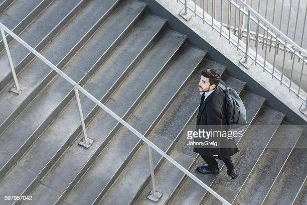 Businessman walking up stairs on work commute