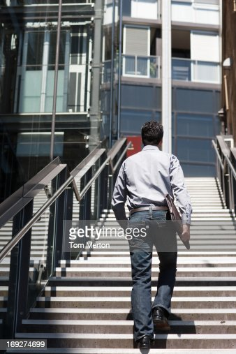 Businessman walking up stairway, rear view : Stock Photo