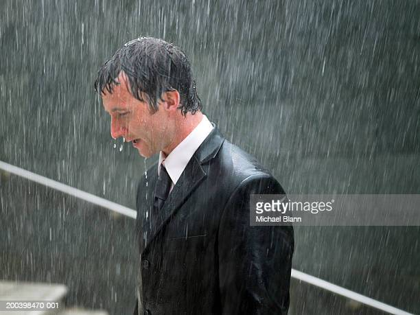 Businessman walking up steps in rain, profile, close-up