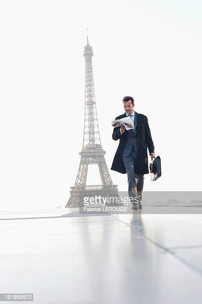 Businessman walking with briefcase reading newspaper with the Eiffel Tower in the background, Paris, Ile-de-France, France