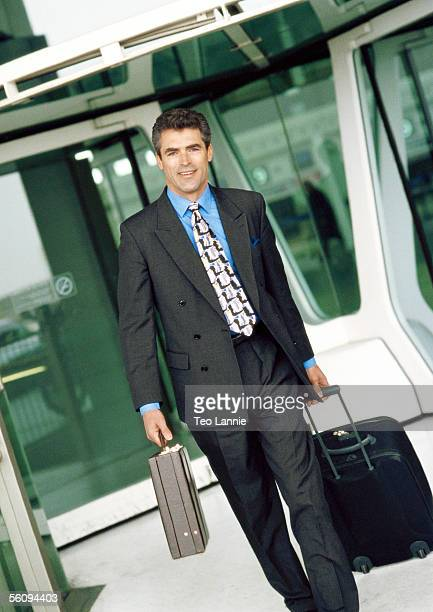 Businessman walking with luggage and briefcase.
