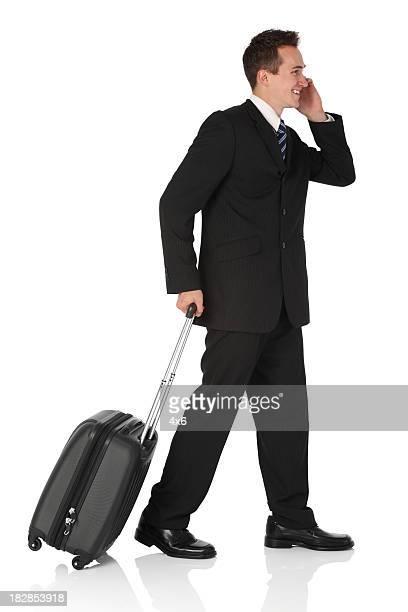 Uomo d'affari camminando con bagagli e parlare sul telefono cellulare