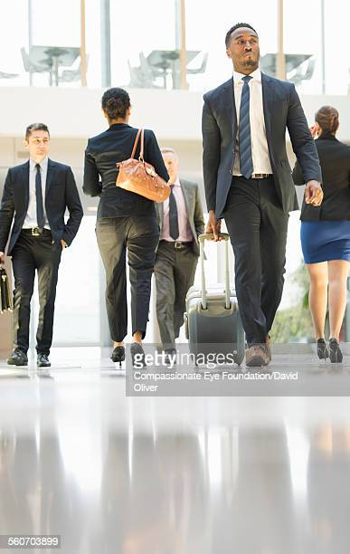 Businessman walking with luggage at airport