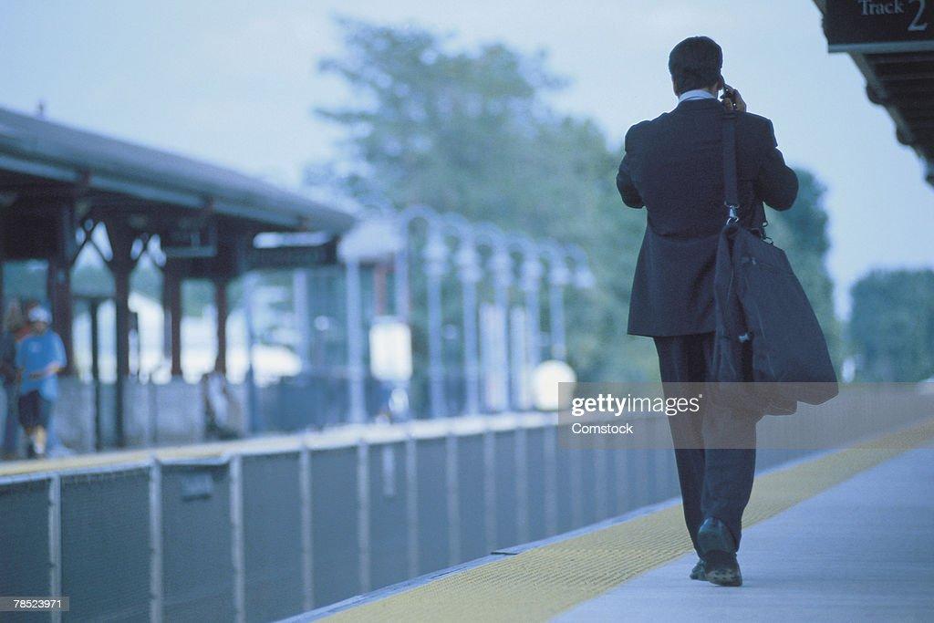 Businessman walking with luggage on train platform : Stock Photo