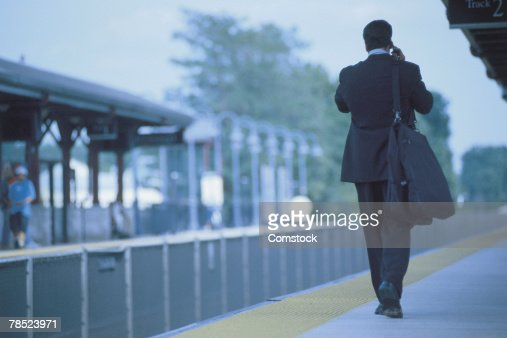 Businessman walking with luggage on train platform : Stock Photo