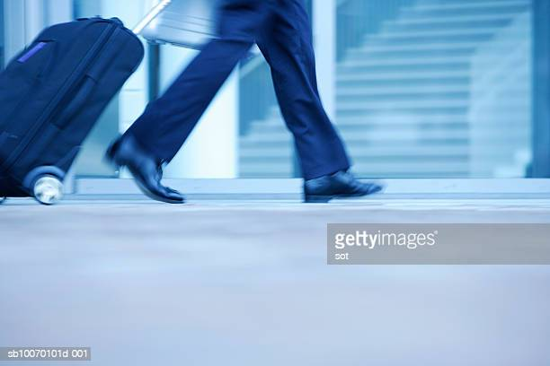 Businessman walking with rolling suitcase, low section
