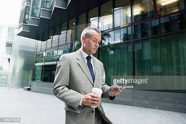 Businessman walking with smartphone and coffee