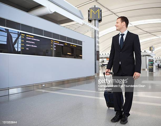 Businessman walking with suitcase at airport