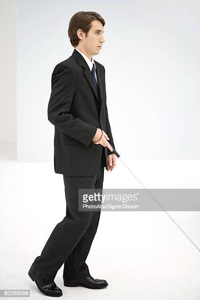 Businessman walking with white cane, side view