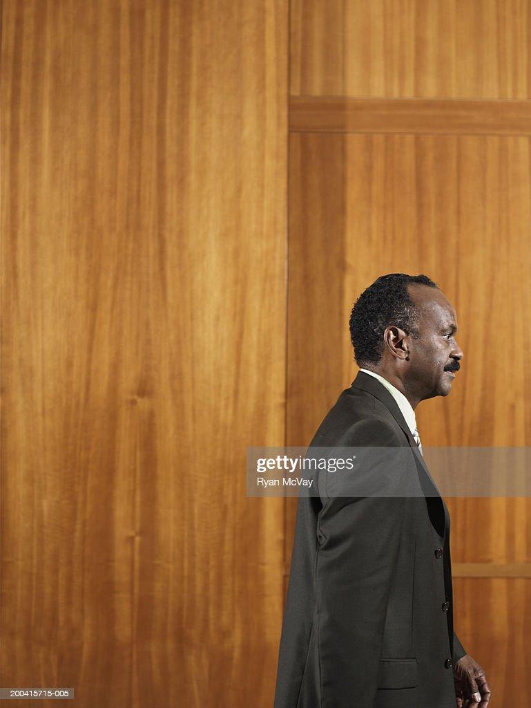 Businessman walking, wood panel background : Stock Photo