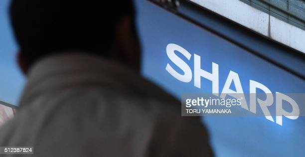A businessman walks before a logo of Japan's electronics giant Sharp in Tokyo on February 26 2016 Japan's centuryold Sharp agreed to be taken over by...