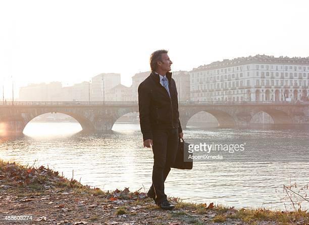 Businessman walks beside river, sunrise