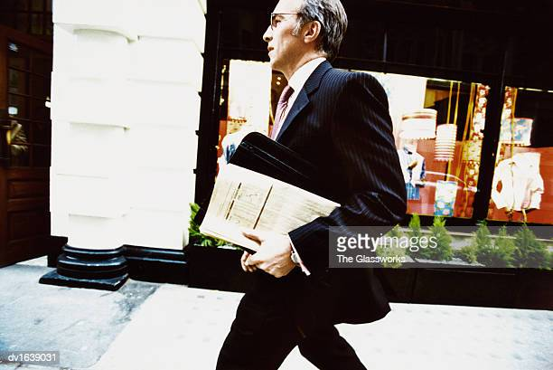 Businessman Walks on a Pavement Carrying a Briefcase and a Folded Newspaper