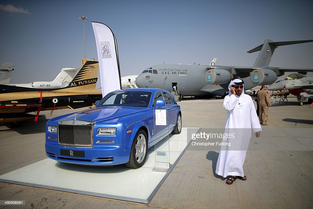 A businessman walks past a Rolls Royce motor car during the Dubai Airshow on November 18 2013 in Dubai United Arab Emirates The Dubai Air Show is the...