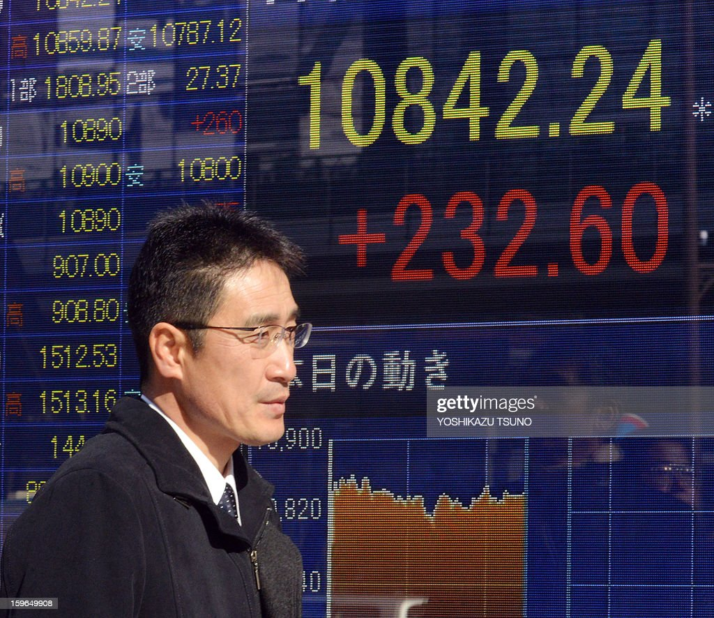A businessman walks past a share price display board in Tokyo on January 18, 2013. Japan's share prices rose 232.60 points to close at the morning session of the Tokyo Stock Exchange, boosted by a weaker yen, upbeat Chinese economic data and solid gains on Wall Street. AFP PHOTO / Yoshikazu TSUNO