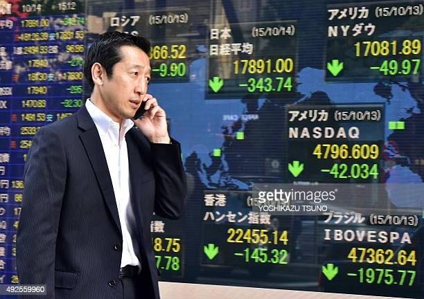 A businessman walks past a share prices board in Tokyo on October 14 2015 Japanese stocks closed 189 percent lower on October 14 amid a lack of...