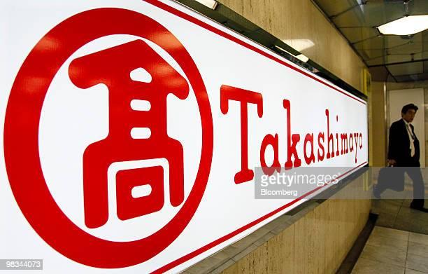 A businessman walks past a sign for Takashimaya Co's department store in the Nihonbashi district of Tokyo Japan on Friday Apr 9 2010 Takashimaya Co...