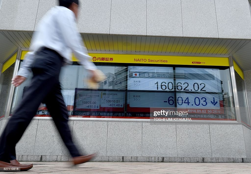 A businessman walks past a stocks display in the window of a security company in Tokyo on May 2, 2016. Tokyo's benchmark Nikkei 225 index slumped 3.62 percent, or 604.03 points, to 16,062.02 by the break, as the surging yen hit exporters in holiday-thinned trade. / AFP / TOSHIFUMI