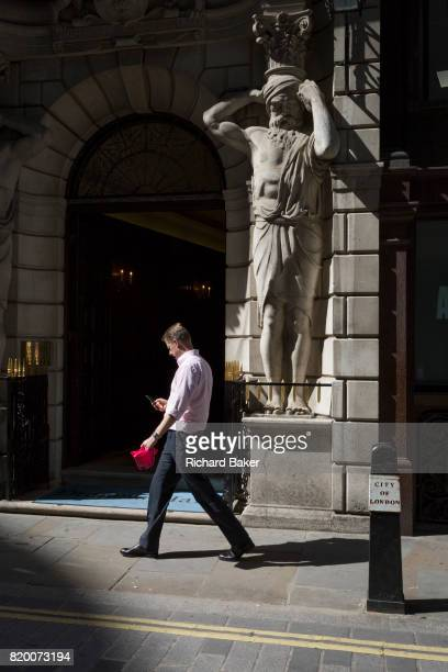 A businessman walks past an Atlantes figure by the sculptor HA Pegram at the entrance of Drapers' Hall livery company in Throgmorton Street on 17th...