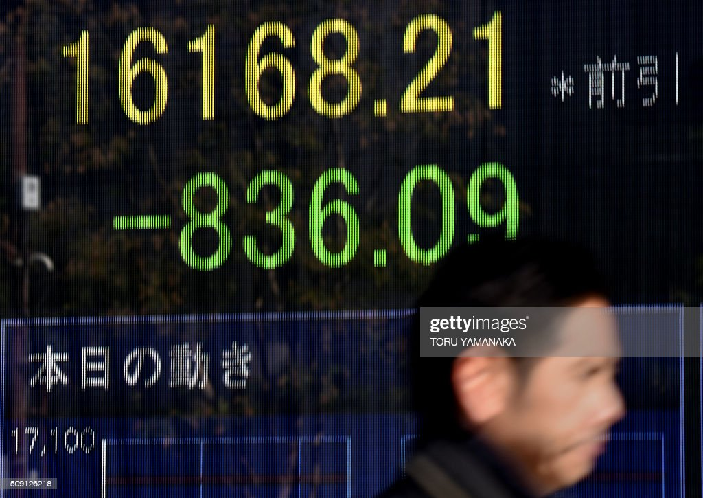 A businessman walks past an electric quotation board flashing the Nikkei key index of the Tokyo Stock Exchange (TSE) in front of a securities company in Tokyo on February 9, 2016. Tokyo shares tumbled nearly five percent, extending a global sell-off as a stronger yen dented exporters and after oil prices tanked again on fears of a deepening economic slowdown. AFP PHOTO/Toru YAMANAKA / AFP / TORU YAMANAKA