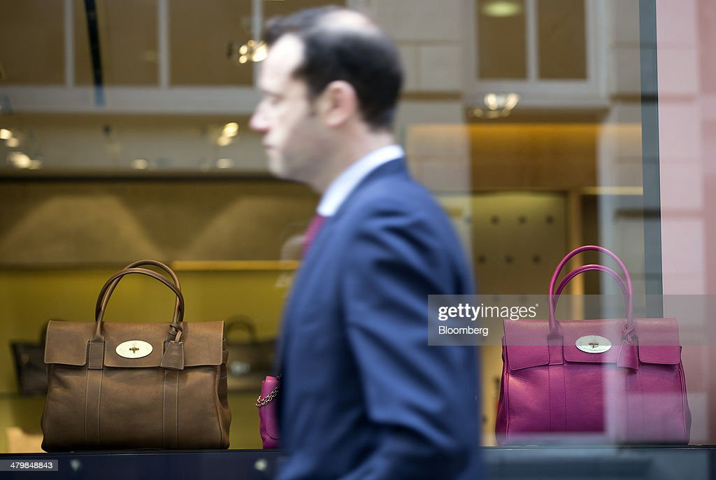 A businessman walks past ladies handbags displayed in the window of a Mulberry Group Plc luxury store in London, U.K., on Thursday, March 20, 2014. Mulberry Group said Bruno Guillon will step down as chief executive officer after two years during which the British luxury handbag maker lost two-thirds of its market value. Photographer: Simon Dawson/Bloomberg via Getty Images