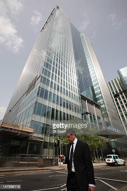 A businessman walks past the Canary Wharf headquarters of Barclays Bank who have been fined 290 million GBP for manipulating the Libor interbank...