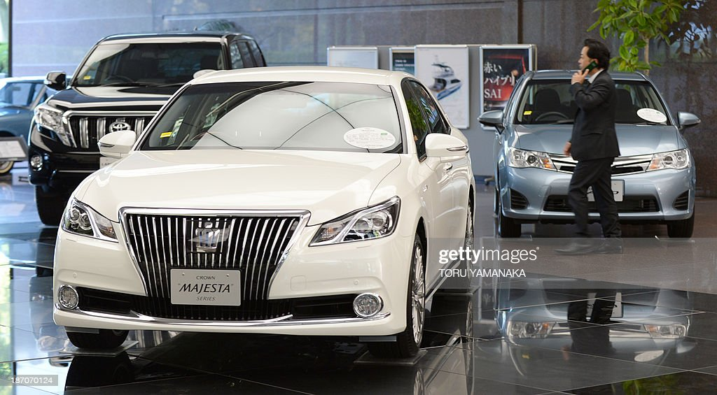 A businessman walks past vehicles at the showroom of the head office of Japan's auto giant Toyota Motor in Tokyo on November 6, 2013. Toyota said on November 6 that its half-year net profit soared 82.5 percent while it raised its annual earnings forecast as a weak yen and improving sales in North America boosted its bottom line. AFP PHOTO/Toru YAMANAKA