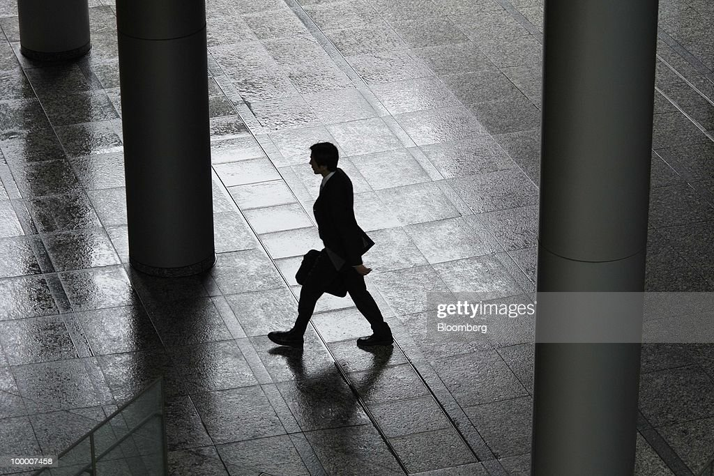 A businessman walks through a building in Tokyo, Japan, on Thursday, May 20, 2010. Japan's economy grew less than forecast in the first quarter as an export-led recovery failed to stoke consumer spending, putting pressure on the central bank to do more to end deflation as it begins a two-day meeting. Photographer: Akio Kon/Bloomberg via Getty Images
