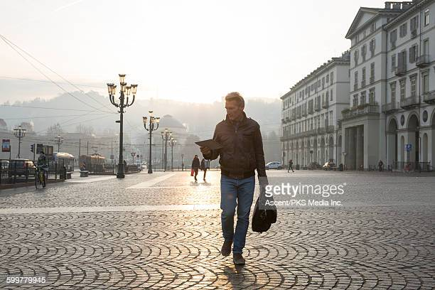 Businessman walks through piazza, holding tablet