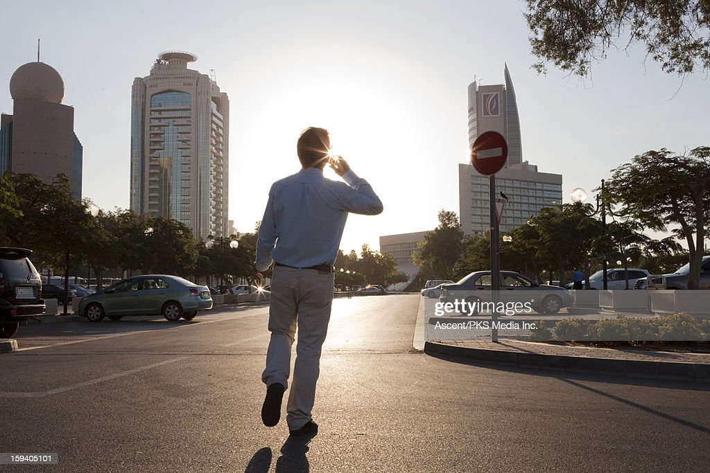 Businessman walks towards car, talks on cell phone : Stockfoto