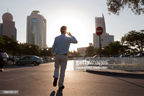 Businessman walks towards car, talks on cell phone : Stock Photo