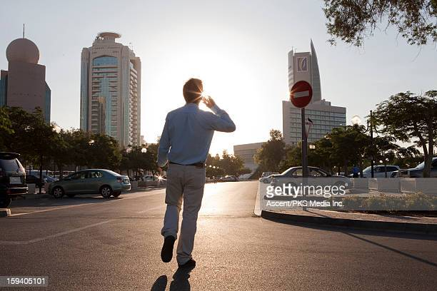 Businessman walks towards car, talks on cell phone