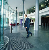 Businessman Walks Towards Revolving Doors as He Leaves an Office Building