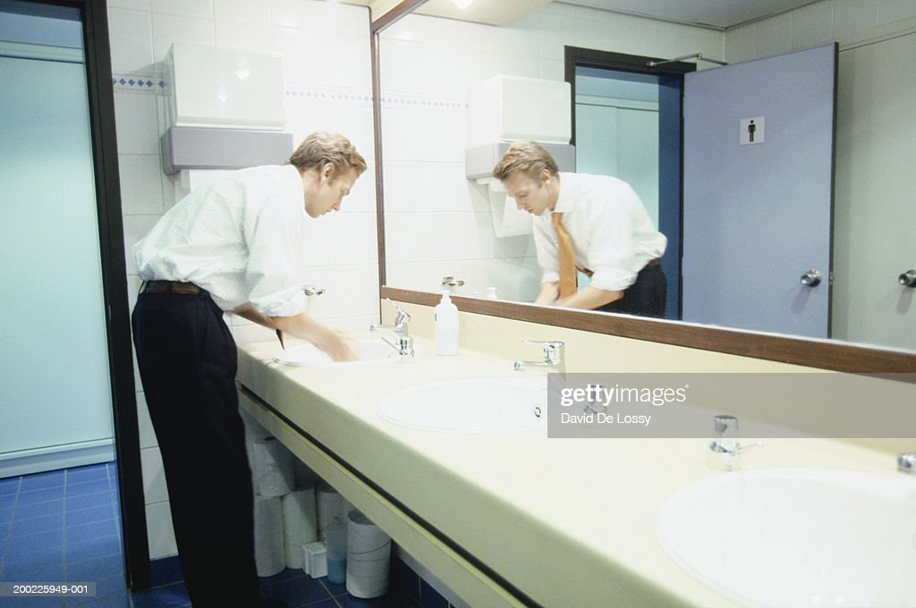 Businessman washing hands in bathroom