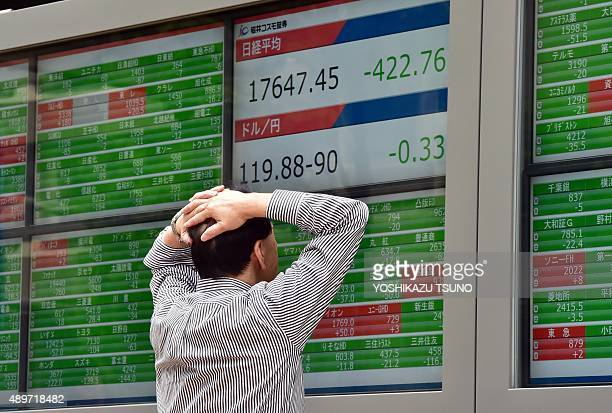 A businessman watches a share prices board in Tokyo on September 24 2015 Japan's share prices fell 42276 points to close at 1764745 points at the...