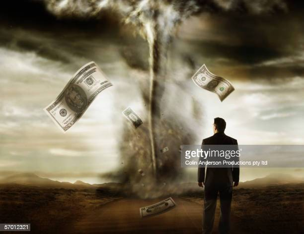 Businessman watching dollar bills flying out of a tornado
