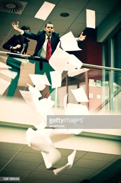 Geschäftsmann vor Zeitungen fliegen über Balkon