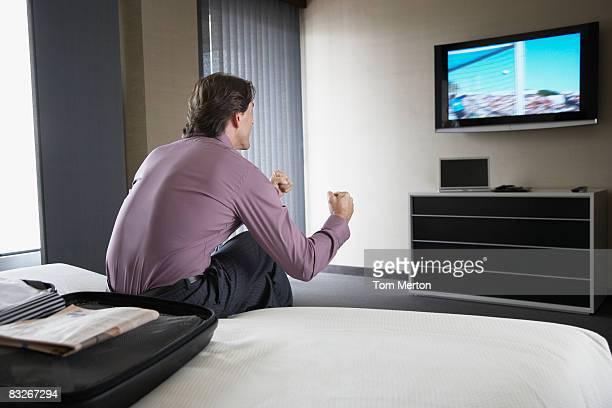Empresario mirando Televisor en habitación de hotel