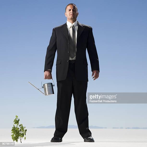 Geschäftsmann gießen einer Pflanze in der Wüste