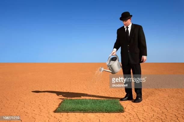 Geschäftsmann gießen Rasen in der Wüste