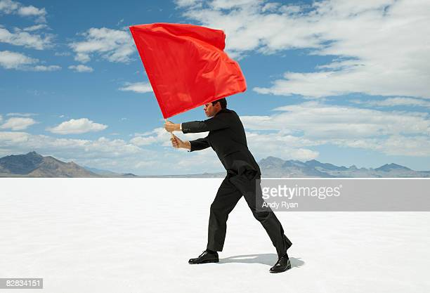 Businessman Waving Red Flag on Salt Flat