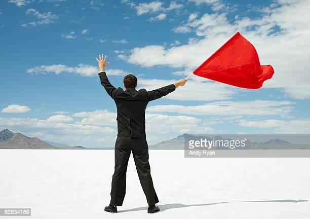 Businessman Waving Red Flag on Salt Flats.