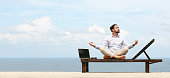 Businessman wearing a suit on deck chair doing Yoga on the beach