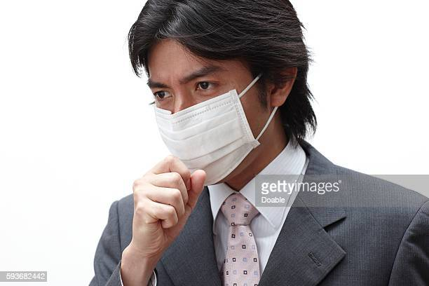 Businessman wearing a surgical mask and coughing