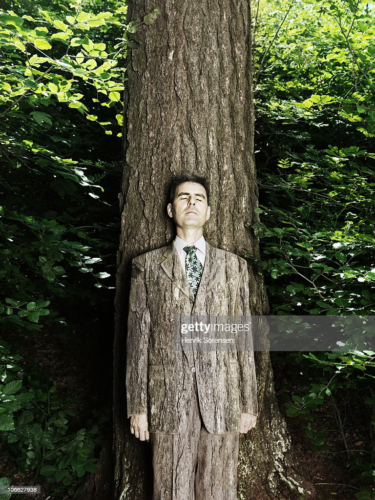 Businessman wearing bark textured suit in woods
