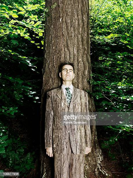 Businessman wearing bark textured suit in woods