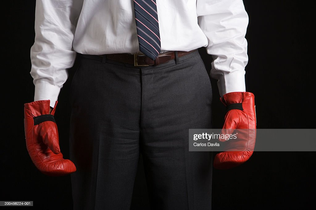 Businessman wearing boxing gloves, mid section, close-up : Stock Photo