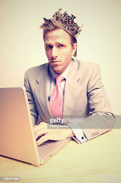 Businessman Wearing Crown and Working on Laptop