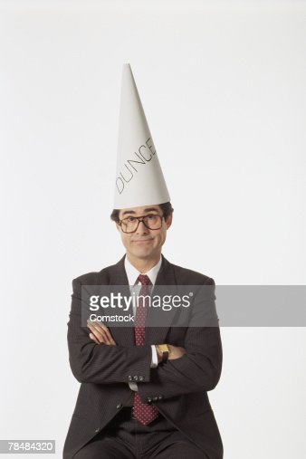 Businessman wearing dunce cap