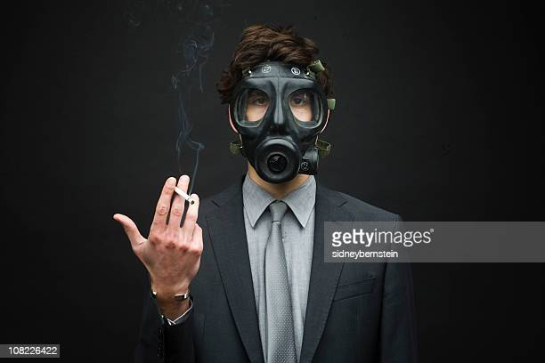Businessman Wearing Gas Mask and Smoking Cigarette